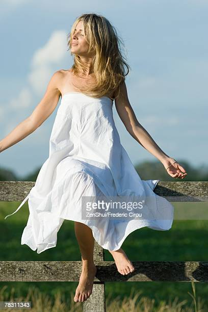 Young woman sitting on top of wooden fence in sun, eyes closed