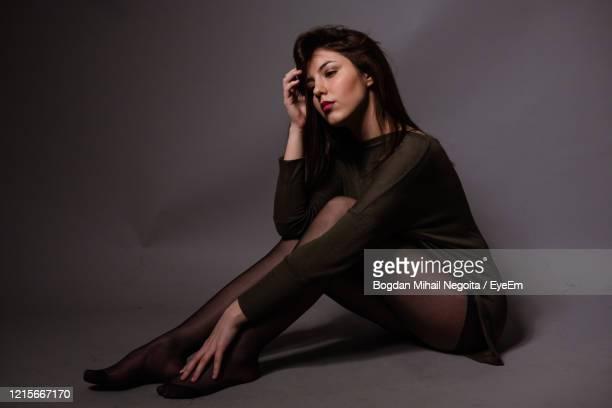 young woman sitting on wall against gray background - bogdan negoita stock pictures, royalty-free photos & images