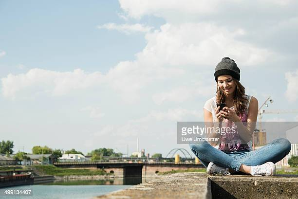 Young woman sitting on wall using cell phone
