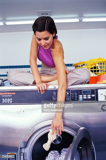 young woman sitting on washer, throwing laundry into machine - bend over woman stock pictures, royalty-free photos & images