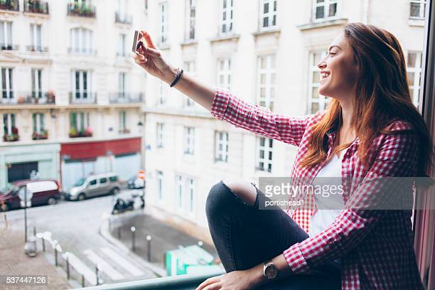 Young woman sitting on window sill and making selfie
