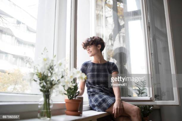 Young woman sitting on window sill at home