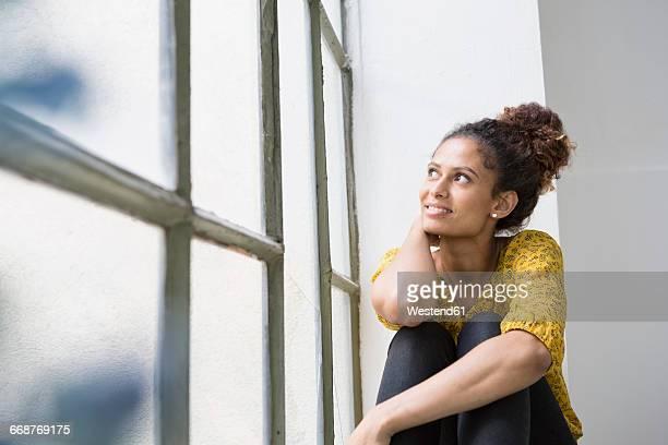 young woman sitting on window sill, looking out of window - focus op achtergrond stockfoto's en -beelden