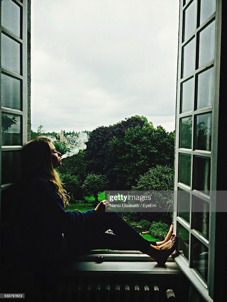 Young Woman Sitting On Window Sill : Foto stock
