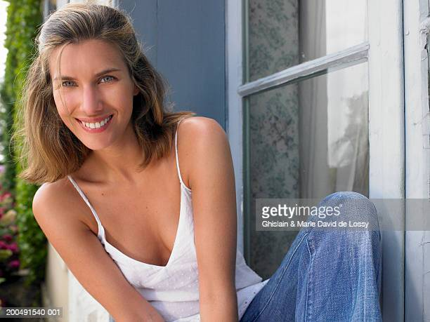 young woman sitting on window sill, smiling, close-up, portrait - cleavage close up stock photos and pictures