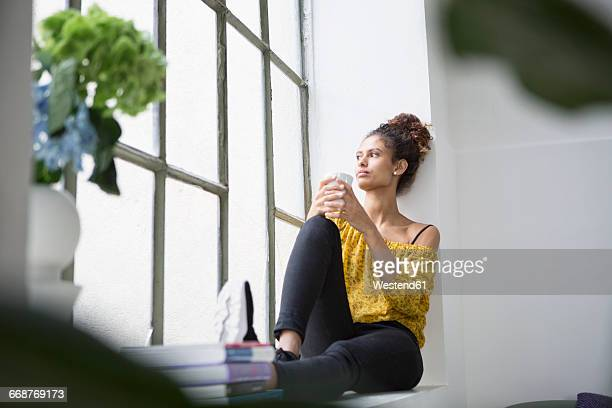 Young woman sitting on window sill with a cup of coffee