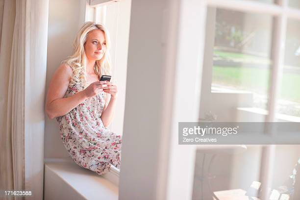 Young woman sitting on windowsill holding smartphone