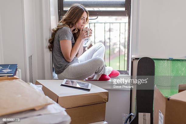 Young woman sitting on windowsill of new home, holding hot drink, cardboard boxes in room