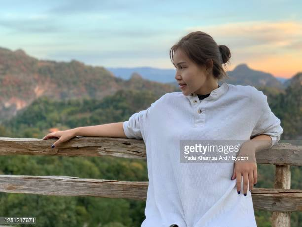 young woman sitting on wood against sky - railings stock pictures, royalty-free photos & images