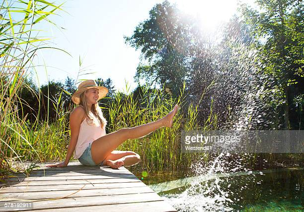 Young woman sitting on wooden boardwalk splashing with water of a pond