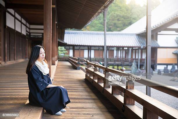 Young woman sitting on wooden deck in Tofukuji temple, Kyoto