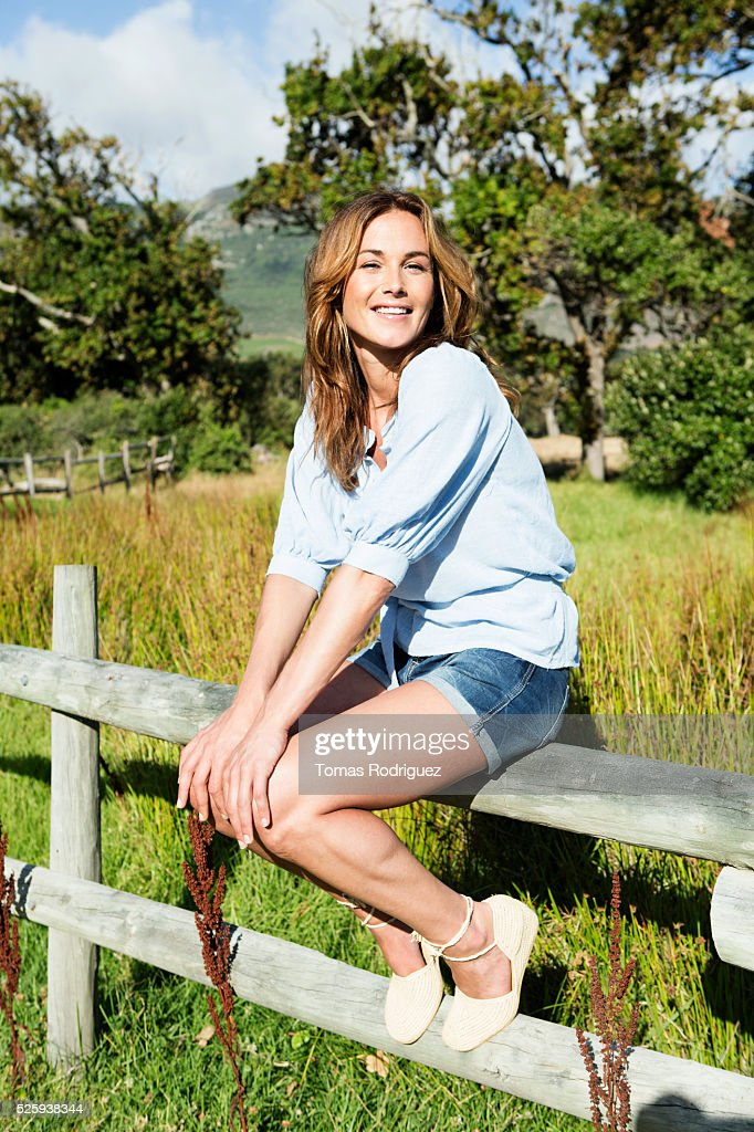 Young woman sitting on wooden fence : Stockfoto