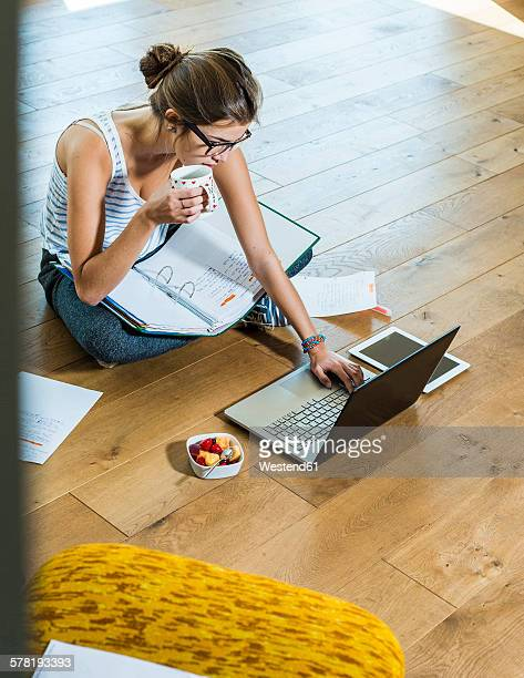 Young woman sitting on wooden floor with file folder and laptop