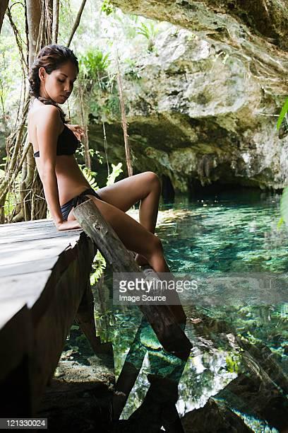 Joven mujer sentada sobre escalera de madera, Grande Cenote