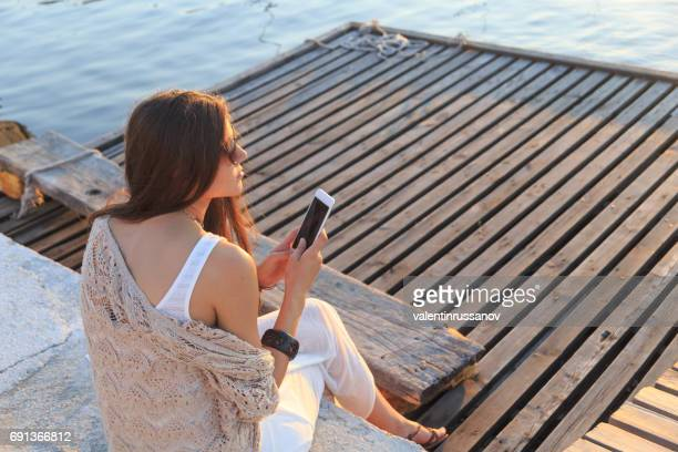 young woman sitting on wooden pier and using smart phone - off shoulder stock pictures, royalty-free photos & images