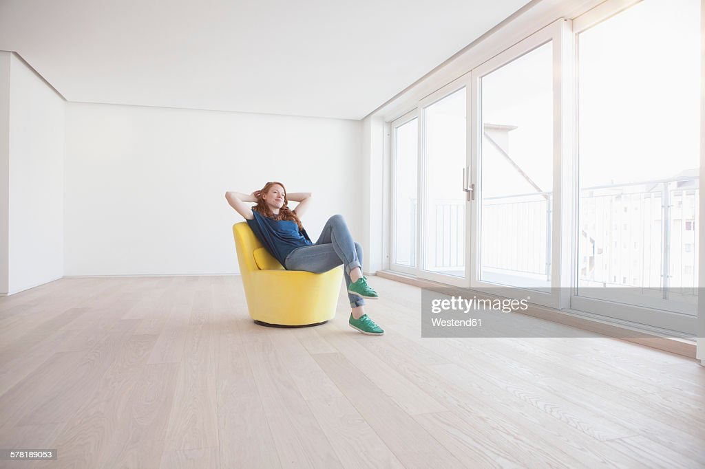 Young woman sitting on yellow armchair in her empty living room : Foto de stock