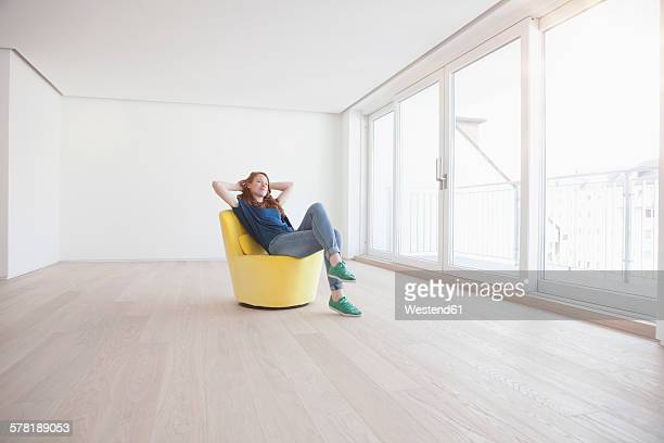 young woman sitting on yellow armchair in her empty living room - sitzen stock-fotos und bilder