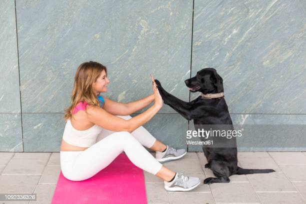 young woman sitting on yoga mat doing relaxation exercise with her black dog - animal tamer stock photos and pictures