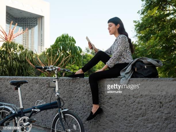 若い女性は、市内でウーチドに座って、デジタルタブレットを使用して - メキシコ北部 ストックフォトと画像