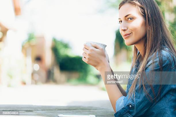 Young woman sitting outdoors and drinking coffee