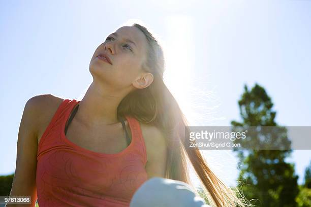 Young woman sitting outdoors, looking up
