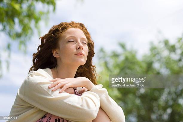 Young woman sitting outdoors with eyes closed