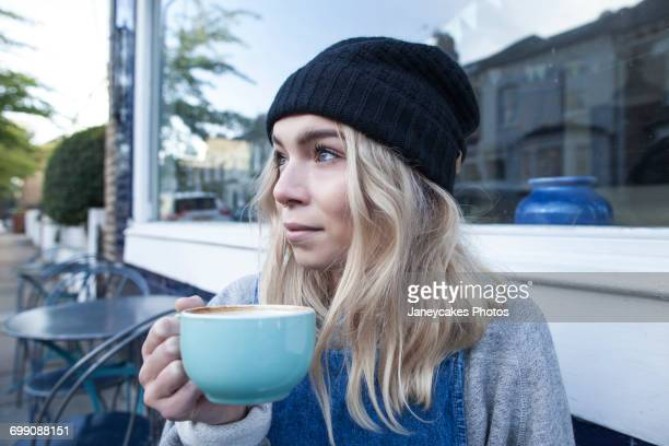 Young woman sitting outside cafe, drinking cup of tea
