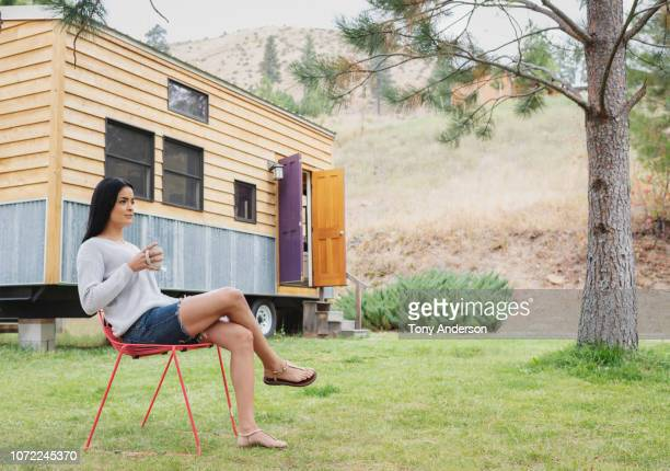 young woman sitting outside her tiny house - gambe accavallate foto e immagini stock