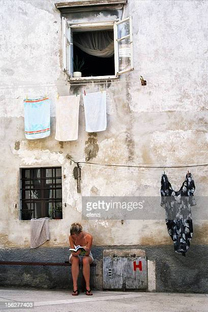 Young Woman Sitting Outside of House