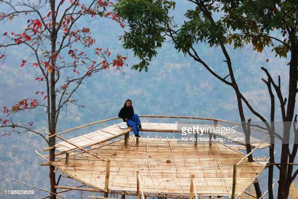 young woman sitting over built structure against trees in forest - ko ko htike aung stock pictures, royalty-free photos & images