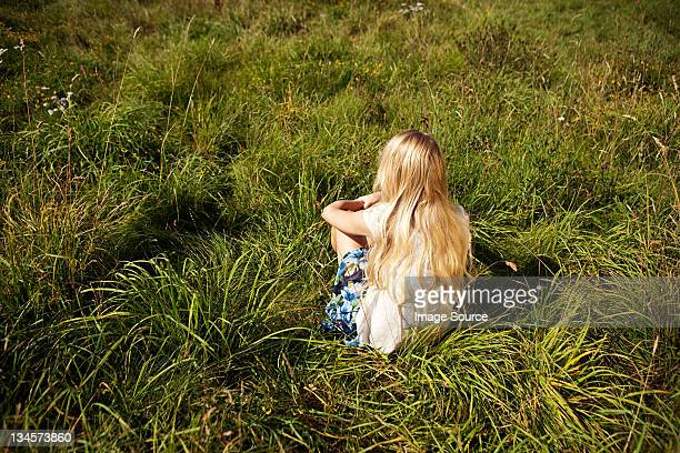 Young woman sitting peacefully in a field
