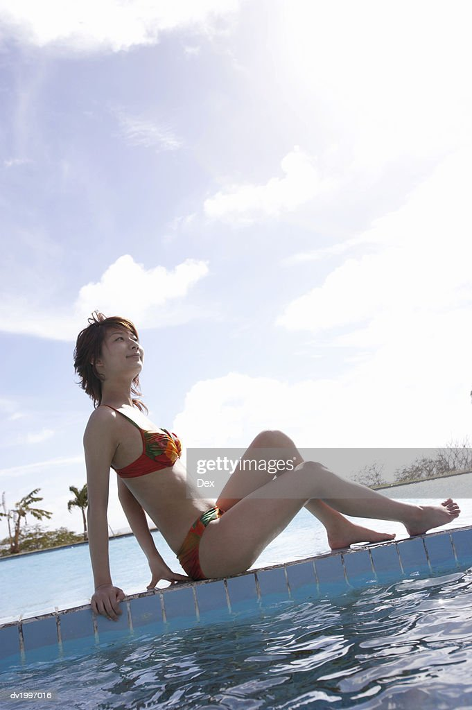 Young Woman Sitting Poolside : Stock Photo