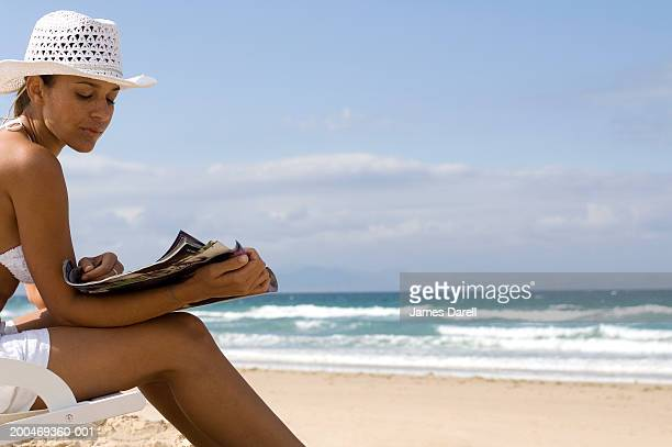 Young woman sitting reading magazine on beach, side view