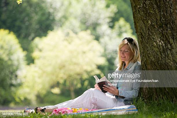 Young woman sitting under tree on sunny day and reading book
