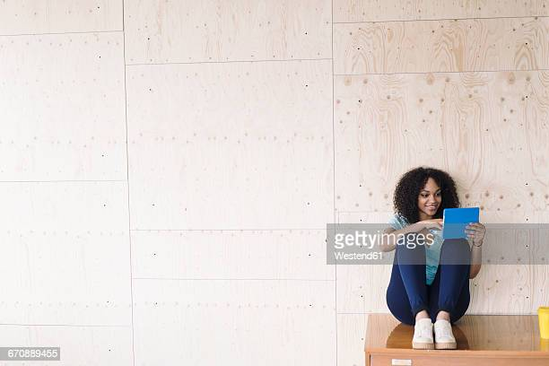 Young woman sitting under white board using laptop