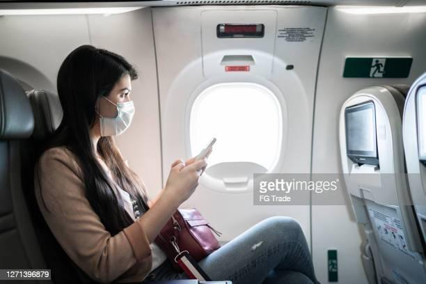 junge frau sitzt mit telefon auf dem flugzeugsitz tragen gesichtsmaske - lateinamerika stock-fotos und bilder