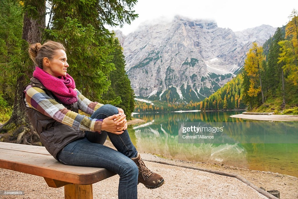 Young woman sitting while on lake braies, italy : Stock Photo
