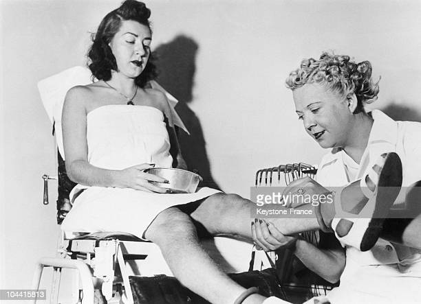 A young woman sitting while undergoing hairremoval at the Beatiderm Institute of Electrolysis with the employee Georgia COLEMAN beside her in New...