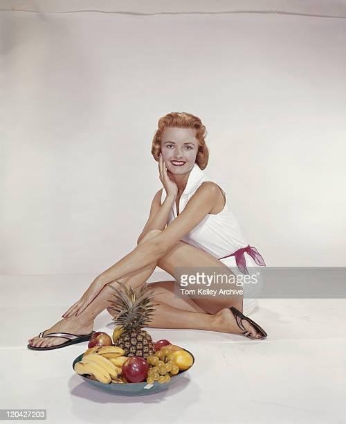 座る若い女性のフルーツのボウル、笑顔、ポートレート