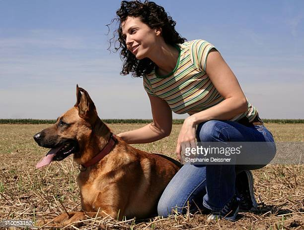 young woman sitting with dog in field - young hairy pics stock photos and pictures
