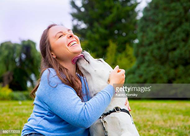 young woman sitting with dog in park, dog licking womans face - licking stock pictures, royalty-free photos & images