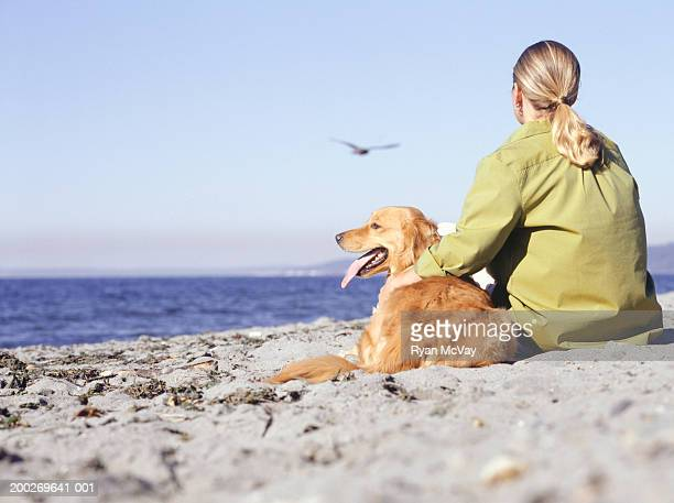 Young woman sitting with Golden Retriever on beach