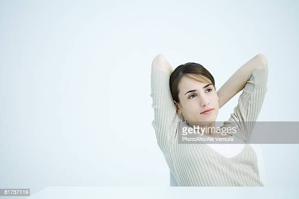 Young woman sitting with hands behind head