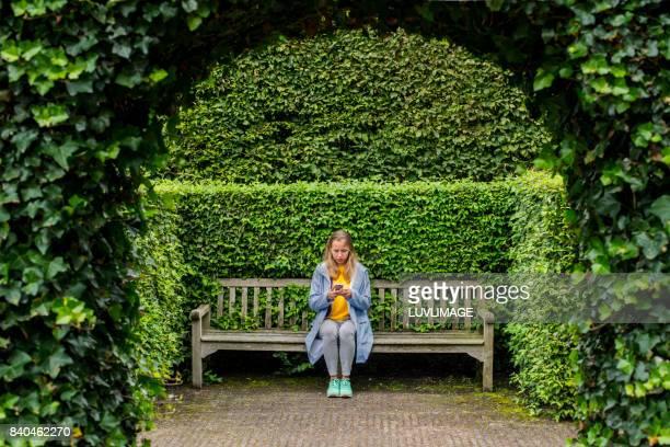 young woman sitting with mobile phone. - al centro foto e immagini stock