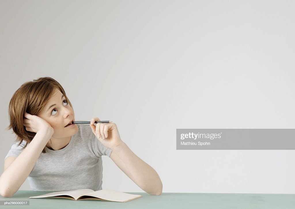 Young woman sitting with open notebook, holding pencil to mouth : Stock Photo