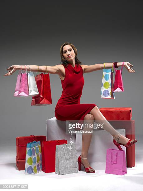 young woman sitting with shopping bags, bags hanging on arms, portrait - excess stock pictures, royalty-free photos & images