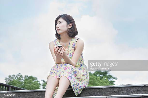 young woman sitting with smartphone,sky background - 目をそらす ストックフォトと画像