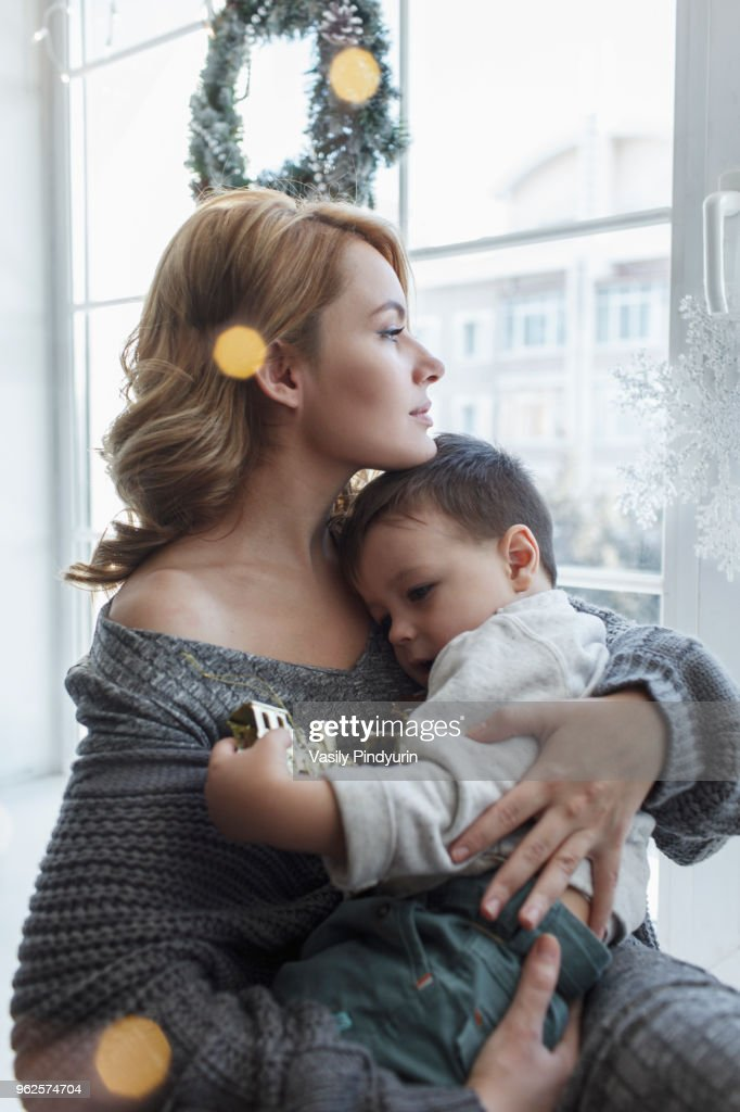 Young woman sitting with son by window at home : Stock Photo