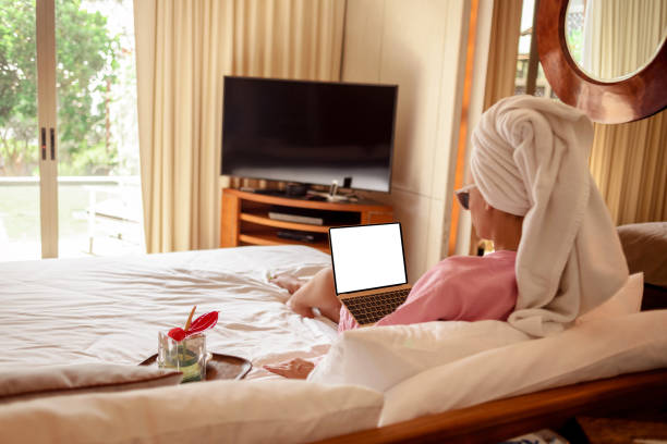 Young woman sitting with towel on her head on the bed in modern bedroom with TV, laptop and other fashion decorations.