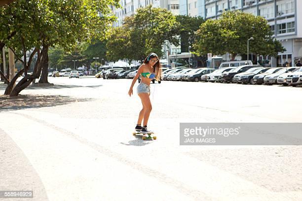 Young woman skateboarding along sidewalk, Copacabana, Rio De Janeiro, Brazil